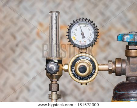 Pressure gage and valves of gas argon on steel wall background.