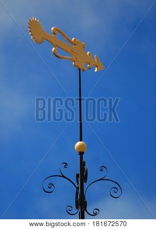 Stylized gold fish weathervane on black rod with decorative iron wor,k.