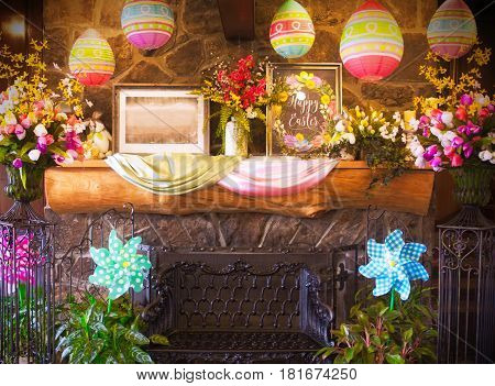 A stone fireplace with a metal bench in front decorated with easter flowers and paper lanterns hanging from the ceiling