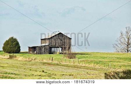 An old barn of gray wood boards converted to storage shed in a fenced pasture in a green spring countryside landscape