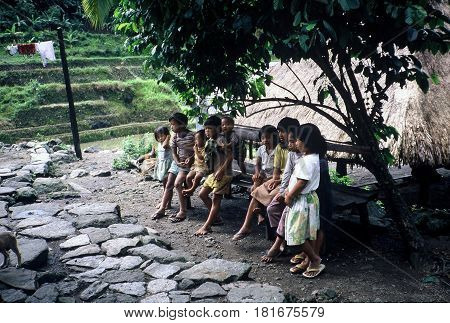 BANAUE, IFUGAO / PHILIPPINES - CIRCA 1990: Ifugao children sit on a bench in a small village in the rice terraces area near Banaue.