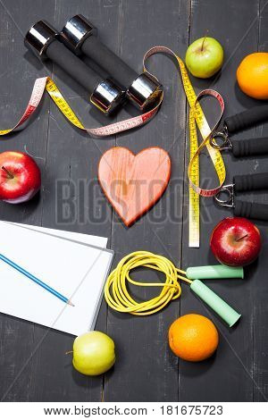 Heart, Fruit And Dumbbells. Fitness, Healthy Lifestyle On A Black Wooden Background