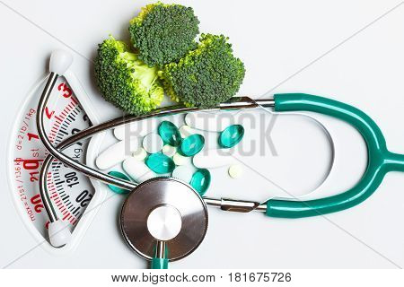 Diet healthy eating weight control and health care concept. Closeup green broccoli stethoscope pills on white scales choice between