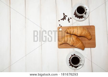 cup of coffee and a croissant on a white wooden table