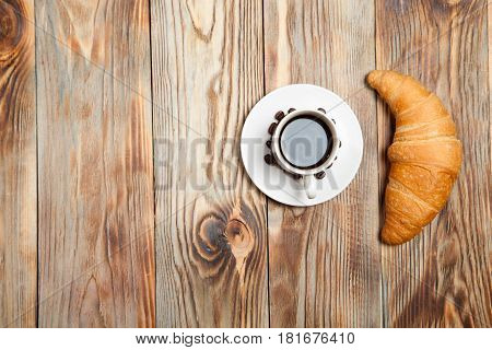cup of coffee and a croissant on a wooden table