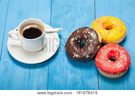 Cup with coffee and donuts on a blue wooden table