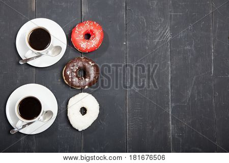Two cups with coffee and donuts on a black wooden table