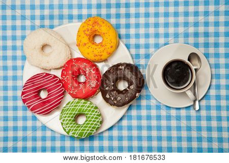 cup with coffee and donuts on a blue table