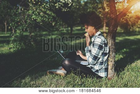 Black female student is eating apple while sitting on grass in city park with laptop on sunny summer day mixed teenage girl with curly afro hair is sitting on spring meadow with net-book and studying