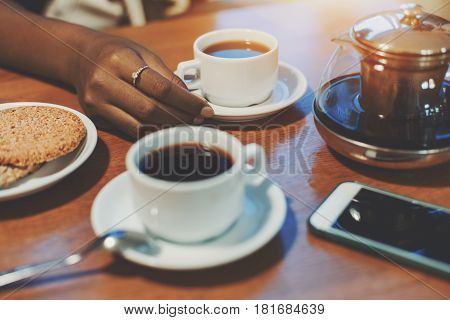 Hand of young black girl touching cup with delicious tea on table with sesame biscuits teapot one more cup and smartphone biracial teenager arm holding white saucer while meeting during breakfast