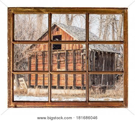 Old rustic barn in cottonswood as seen  through vintage, grunge, sash window with dirty glass