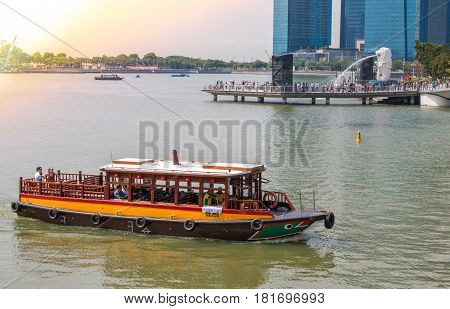 MARINA BAY SINGAPORE - MAR 21 2017 : Tourists enjoy a boat sightseeing tour at public Merlion Park Marina Bay in Singapore. Merlion Park is a Singapore landmark and major tourist attraction.