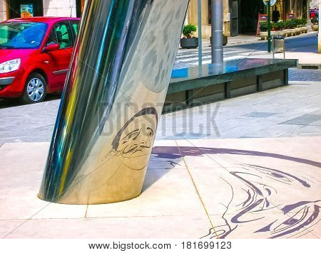 Figueres, Spain - May 07, 2007: The unclear image on the ground is reflected on to the cylindrical pillar to form the image of the Salvador Dali with his famous moustache at Figueres, Spain on May 07, 2007