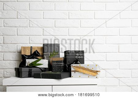 Stylish present boxes on white brick wall background