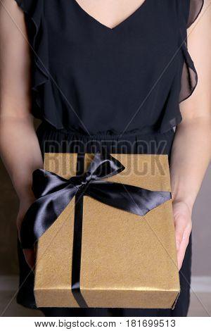 Female hands holding present box closeup