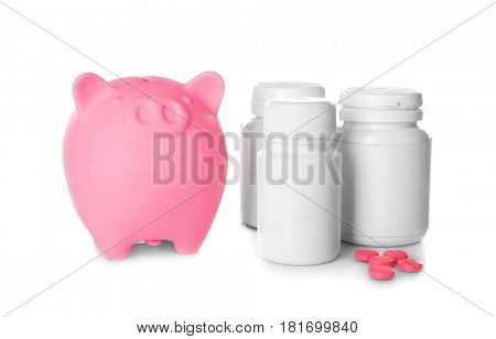 Piggy bank with bottle of pills on white background