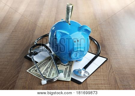 Piggy bank with stethoscope and clipboard on table