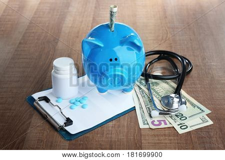 Piggy bank with stethoscope and dollars on table