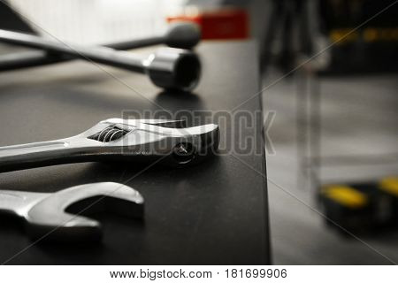 Wrenches on table in car repair shop, closeup