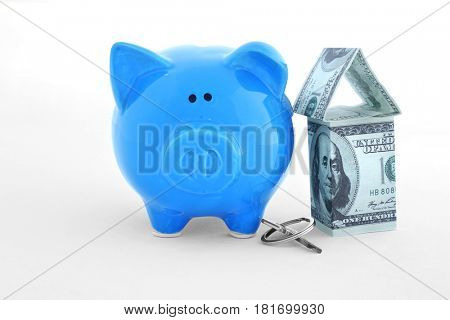 Savings concept. Piggy bank with key and house figure on white background