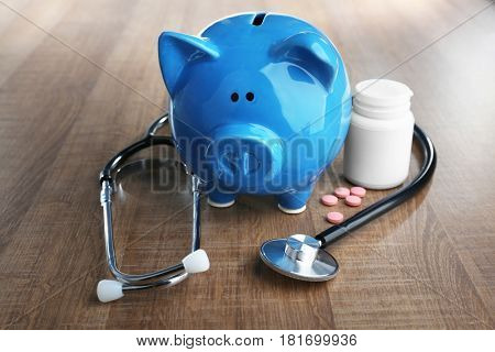 Piggy bank with stethoscope and pills on table