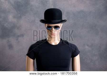 male display dummy with sunglasses and bowler hat in front of gray background