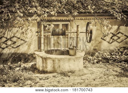 retro image of water well in rural place