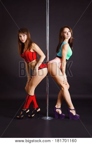Beautiful brunettes dancing on a pole