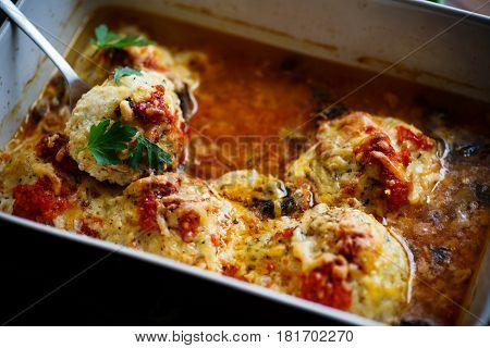 Fish meatballs baked in sauce in ceramic form