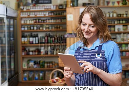 Female Delicatessen Owner In Store With Digital Tablet