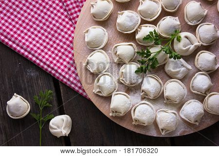 Dumplings raw on a round board. Russian national food. The process of cooking dumplings.top view
