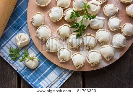 Dumplings raw on a round board. Russian national food. The process of cooking dumplings.