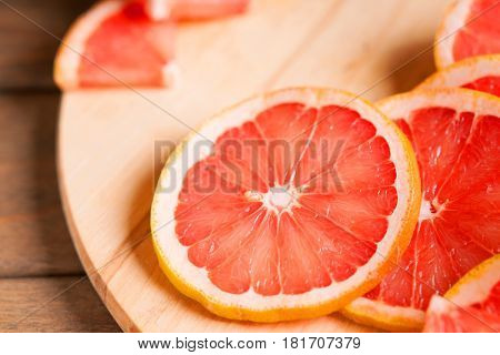 Photography of a grapefruit slice on a wooden cutting board