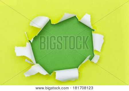 Yellow ripped open paper on green paper background