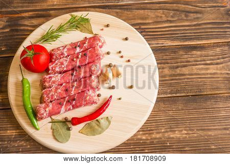 Raw cevapcici dish of mixed meats the food of the Balkans. Minced meat and bacon.