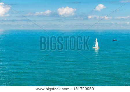 Single sail boat adrift on the ocean.