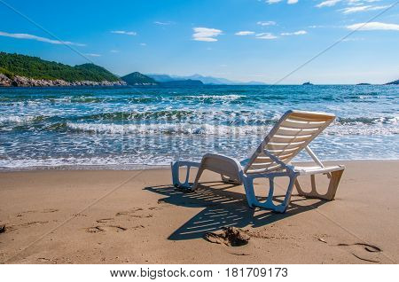 Lonesome deck chair looking of someone to sit on in front of crashing waves on the beach.