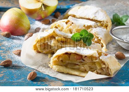 Homemade Apple Strudel With Fresh Apples, Nuts And Powdered Sugar On A Blue Vintage Wooden Backgroun