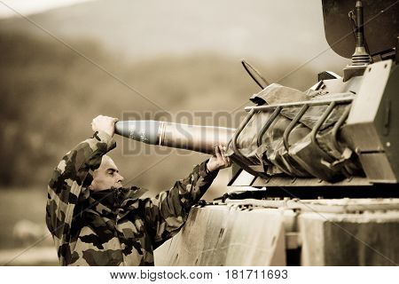 France, the training center of the foreign legion - circa, 2011. The legionnaire submits a combat charge to the side of the AMX-10 tank during the exercises.