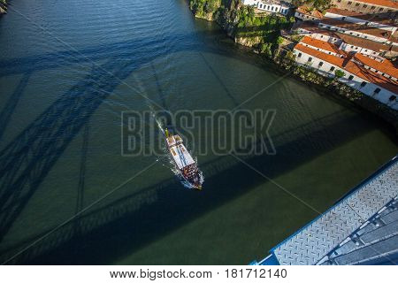 View of Douro river from Dom Luis I Bridge, moving boat and shadow on the water, Porto, Portugal.