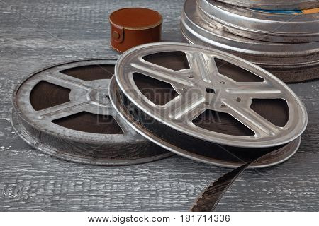 Reels with old film and tin boxes lie on a wooden table