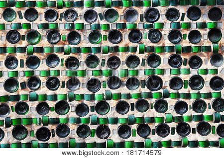 Colorful recycling background texture of empty wine bottles in the wall construction.