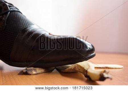 Black patent shoe of young man slipped on a banana peel.
