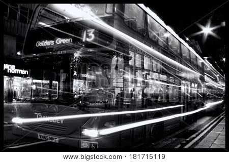 London, UK - Oct 6, 2011: Black & white image of a No 13 red double decker bus at night passing through Oxford Street with light trails
