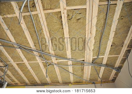 Ceiling construction detail. Close up on ceiling construction details with electricity wire. Building construction gypsum plaster walls and ceiling. Ceiling Joists of Home Under Construction. Attic Insulation with mineral wool. Insulation House.