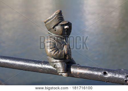 Small bronze statue of Good Soldier Svejk attached to the handrails at Kyivska embankment of the river Uzh in Uzhgorod Ukraine photo