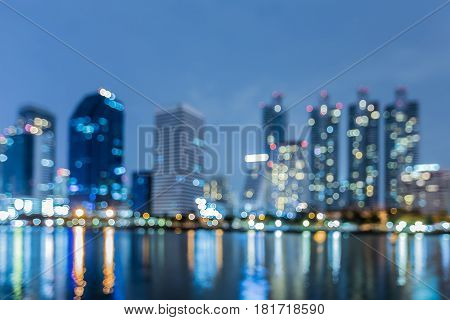 Twilight blurred bokeh Office building light with water reflection abstract background