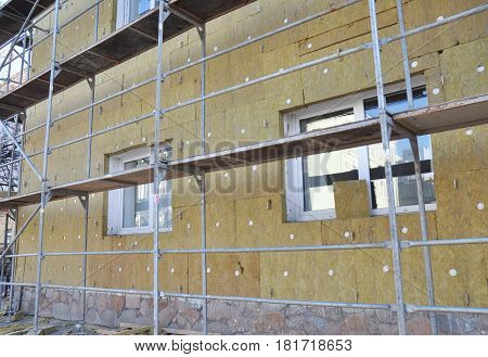 External wall insulation. Solid mineral wool wall insulation. Energy efficiency house wall renovation for energy saving. Exterior house wall heat insulation with mineral wool building under construction.