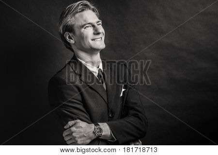 Black and white portrait of buisness man looking away with crossed arms.
