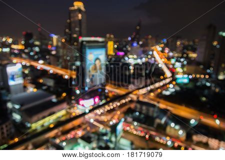 Top view city road interchanged and office building blurred bokeh light night view abstract background